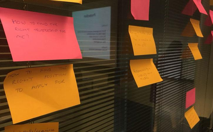 Post it notes wall in a seminar text reads how do I find the right trustee role